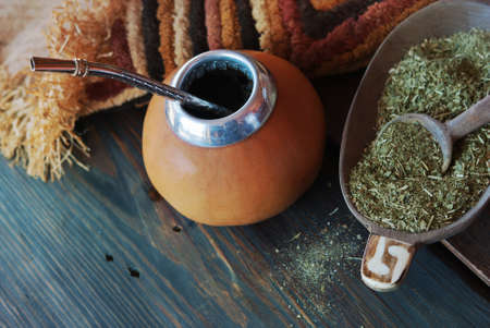 mate infusion: Yerba mate-South American tea, dried leaves in wooden bowl with a wooden mate calabash with tea. Selective focus