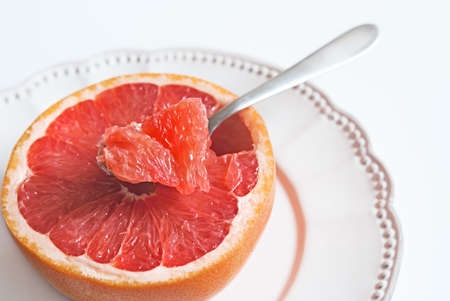 pomelo: Piece of pink grapefruit in a tea-spoon, healthy citrus dessert Stock Photo