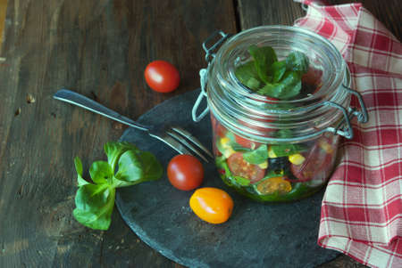 mais: Vegetable fresh salad in glass jars on wooden table,