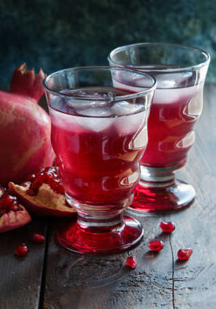 Pomegranate juice in glass and seeds on the wooden table Stock Photo