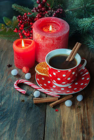 Christmas cup of tea with spice, orange and Christmas decor on the wodden table