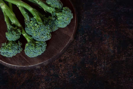 Fresh broccolini on a wooden round board. Space for the text, selective focus Stock Photo