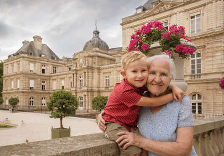 Outdoor portrait of Elderly woman with her grandson in the Luxembourg Gardens