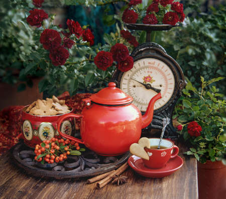 Beautiful flowers and cup of tea with cookies at wooden table, autumn decor Stock fotó