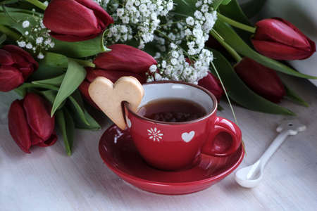 Red tulips and cup of tea with cookie heart on the table Archivio Fotografico - 125805565