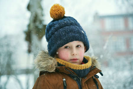 Thinking little boy outdoor at snowfall winter Archivio Fotografico - 125805569