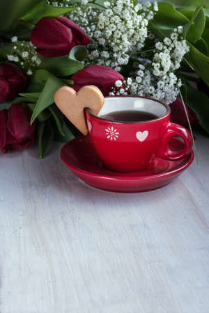 Red tulips and cup of tea with cookie heart on the table Archivio Fotografico - 125805618