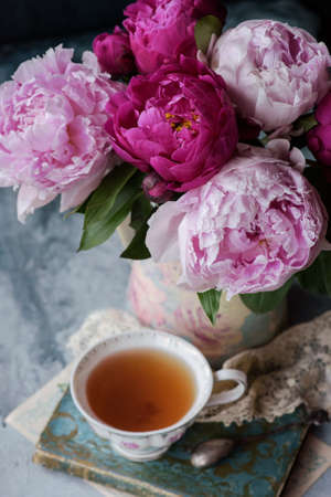 Beautiful flowers peonies in vase and cup of tea on the old book, vintage style decor Archivio Fotografico - 125805622