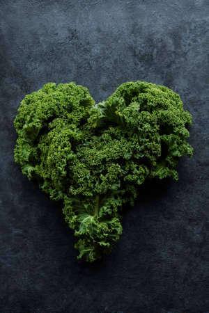 Kale, leaf cabbage in the shape of a heart at the dark background with place for text Archivio Fotografico - 125805632