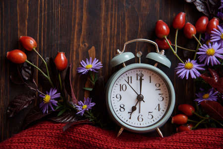 Autumn flowers from the garden with alarm clock at wooden background. Daylight saving time. Archivio Fotografico - 136612250