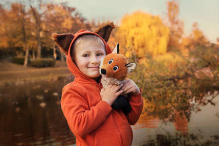 Autumn portrait. Happy smiling boy with soft toy fox on a background of autumn park Archivio Fotografico - 131888394
