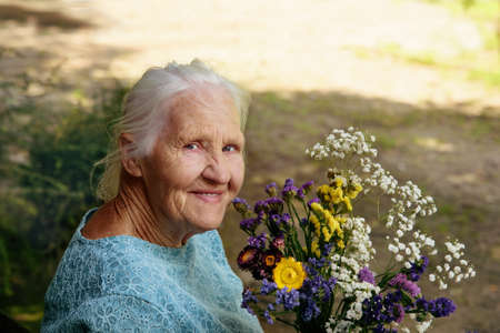 Portrait of the smiling elderly woman with flowers, mother day Archivio Fotografico - 136612294