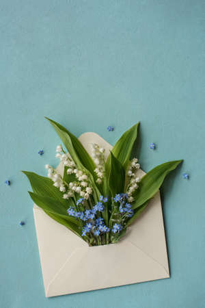Mother's day card with envelope and forget-me-not flowers and lilies of the valley