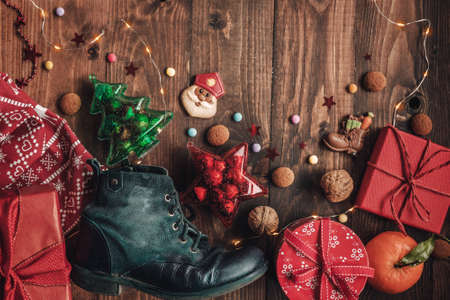Holiday background Saint Nicholas, Sinterklaas, with child shoe, cookies, nut, tangerines, gifts and sweets Stock Photo