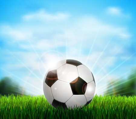 White and black soccer ball on the fresh green glade with grass. Background with blue sky, sunshine and sport equipment for playing football.