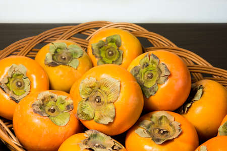 Persimmons on the rattan tray Stock Photo