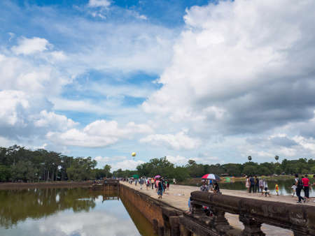 Siem Reap, Cambodia - October 30, 2016: Tourists walking back after visiting Angkor Wat, UNESCO World Heritage site, in Cambodia