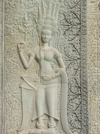 Stone carving of an angel or Apsara on the wall of Angkor Wat, the ancient Hindu temple complex in Cambodia