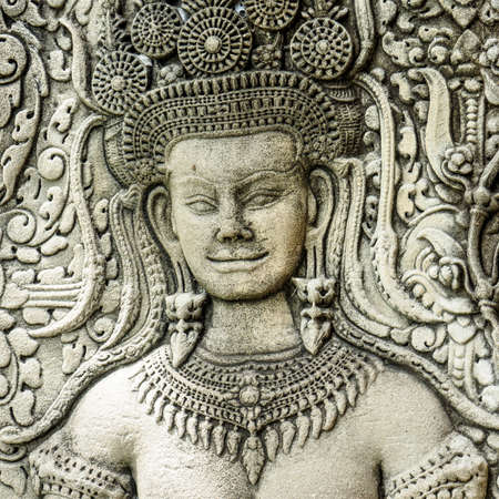 Close up  of face of a stone carving of an angel or Apsara on the wall of Angkor Wat, the ancient Hindu temple complex in Cambodia Stock Photo