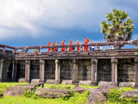 Siem Reap, Cambodia - October 30, 2016: Buddhist monks and novices walking on the stone bridge to enter Angkor Wat