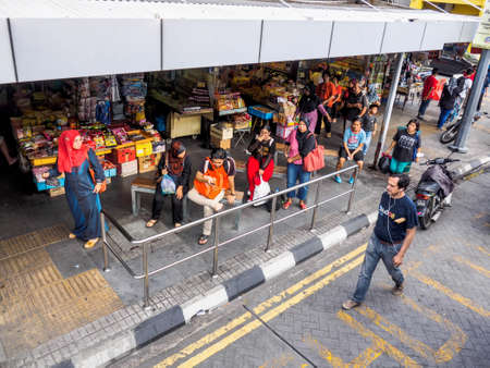 Penang,  Malaysia - June 02, 2016: People waiting for buses at a Bus Stop of Penang Road, George Town, the capital of Penang State, Malaysia.