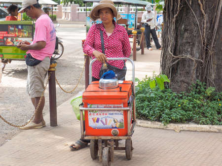 Siem Reap, Cambodia - October 29, 2016:  An unidentified woman selling traditional fruit ice-cream in front of  Preah Ang Chek and Ang Chom Shrine,  Siem Reap, Cambodia,