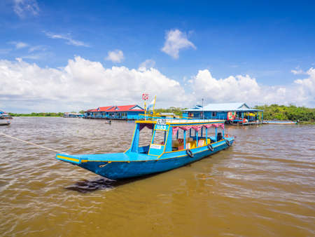 Siem Reap, Cambodia - October 29, 2016: A blue tourist boat docking at  the bank of Tonle Sap, the freshwater lake in Siem Reap, Cambodia, with a floating house and a floating school are at the backgr
