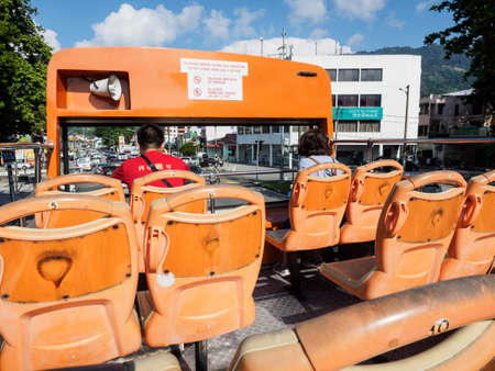 Penang,  Malaysia - April 24, 2017:  The double decker hop-on hop-off bus of Penang  for city tour of  George town, and sightseeing around the island, with two unidentified passengers.