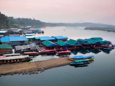 Sangkhlaburi - March 05, 2017: The scenery of  floating village and a part of temporary bamboo bridge  the river in Sangkhlaburi District, Thailand, in the early morning.