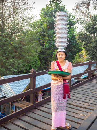Sangkhlaburi, Thailand- March 05, 2017: The unidentified Mon woman selling is selling flowers for tourists at the Mon bridge, while showing her skill in holding empty cooked-rice bowls on her head.