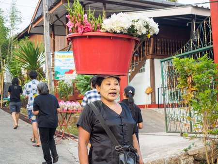 Sangkhlaburi, Thailand- March 05, 2017: The unidentified Mon woman selling flowers for tourists in Sangkhlaburi, while showing her skill in holding flowers in the big red plastic container on her head
