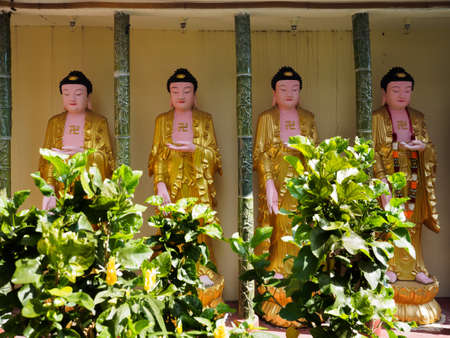 A row of golden buddha statues with swastika symbol on their chests at Kek Lok Si temple, the famous Chinese temple in Georgetown, Penang, Malaysia