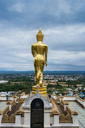 Nan, Thailand - December 16, 2016:  The standing Buddha statute at Phrathat Khao Noi temple, Nan Province, Thailand, standing in front of Nan city view. 報道画像