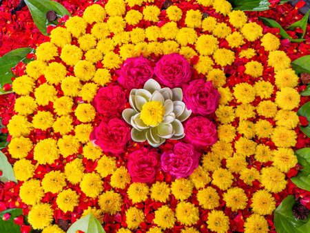 Decoration of  yellow chrysanthemum flowers and red roses as a circle with a plastic flower in the center