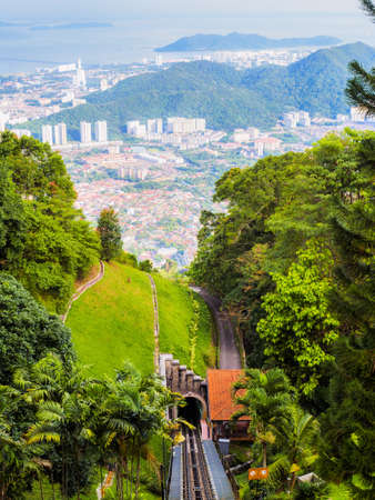 The scenery from Penang Hill station, Penang, Malaysia, showing the track and tunnel in the foreground and the city, mountain and sea in the background.
