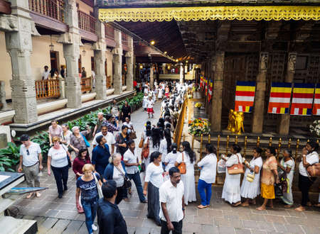 Kandy, Sri Lanka - November 8, 2017: Sri Lankan Buddhists queueing  up at the Temple of Sacred Tooth  Relic for paying respect to the Buddha tooth relic while the group of tourists walking past. 報道画像