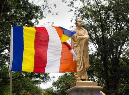 Kandy, Sri Lanka - November 8, 2017 : The statue of Sri Lankan Buddhist Reformer,  the Venerable Anaganika Dharmapala, the reformer of Modern Sri Lanka and the flying flag of Sri Lankan Buddhism. 報道画像