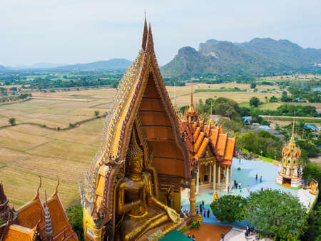 Kamchanaburi, Thailand - January 13, 2018: The scenery of Wat Thamsua or Tiger Cave Temple from high angle showing the giant Buddha statue and visitors at the ground. 報道画像