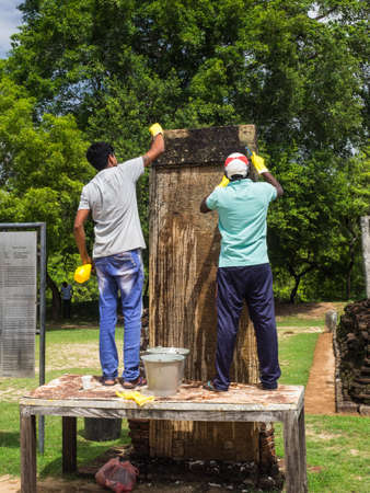 Pollannaruva, Sri Lanka - November 9, 2017: The unidentified workers cleaning the 12th century stone inscriptions in the archaeological park.