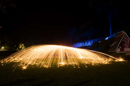 Steel wool light painting in the dark which looks like light umbrella with train track is in the background 写真素材
