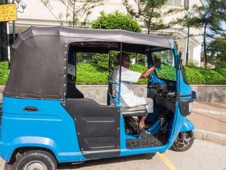 Colombo, Sri Lanka - November 11, 2017: An unidentified elderly driver waiting for passengers  in his blue three-wheeled taxi at the roadside in Colombo, Sri Lanka, 報道画像