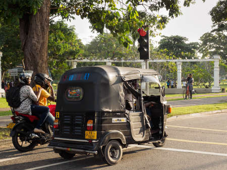 Colombo, Sri Lanka - November 11, 2017: Unidentified men on motorcycle and three-wheeled taxi stop on the road near the park and waiting for green traffic light in Colombo, Sri Lanka,