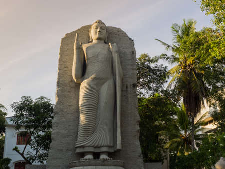 The standing Buddha statue at the Cinnamon Gardens are, Colombo, Sri Lanka, in the evening with trees in the background. 写真素材