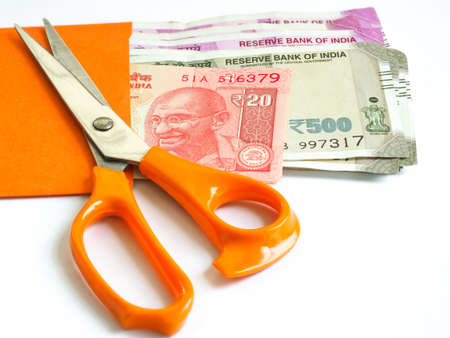 The stainless steel scissors with orange plastic handles is on top of the orange envelope which contain Indian Rupees on the white background 写真素材