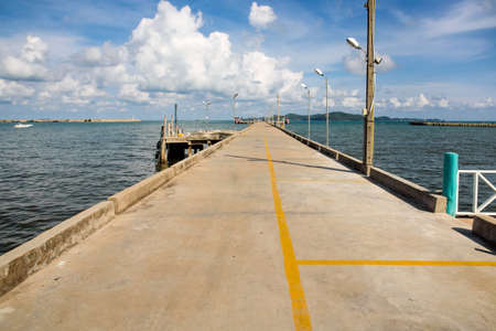 The perspective view of Sribanphe jetty in Rayong Province, Thailand, with the sea, white cloud and blue sky is in the background