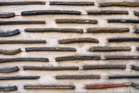 The concrete wall background embedded with root tiles.