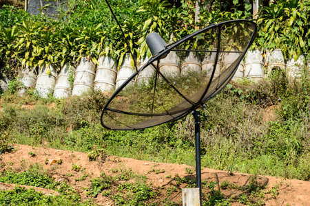 Outdoor TV satellite  receiver dish on the ground in the rural area
