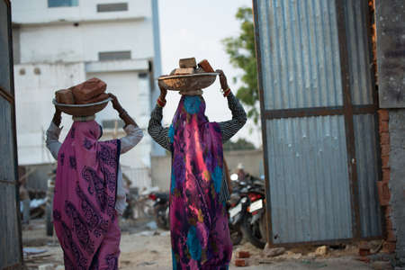 uneducated: Indian women carrying bricks on their heads at a construction site