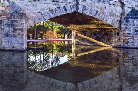 A bridge from Valencia reflects in the water of the park