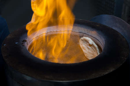 A fire on tandoori oven with naan bread inside.